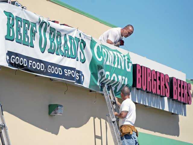 Kevin Jackson, top, and Brian Valladares move a banner as they work to remove old signage Monday from a building slated to house a new Beef 'O' Brady's restaurant on The Old Road in Valencia. Photo by Jonathan Pobre