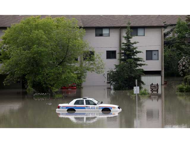 A police car sits stuck in a parking lot of an apartment building after heavy rains have caused flooding, closed roads and forced evacuation in Calgary, Alberta, Canada on Friday.