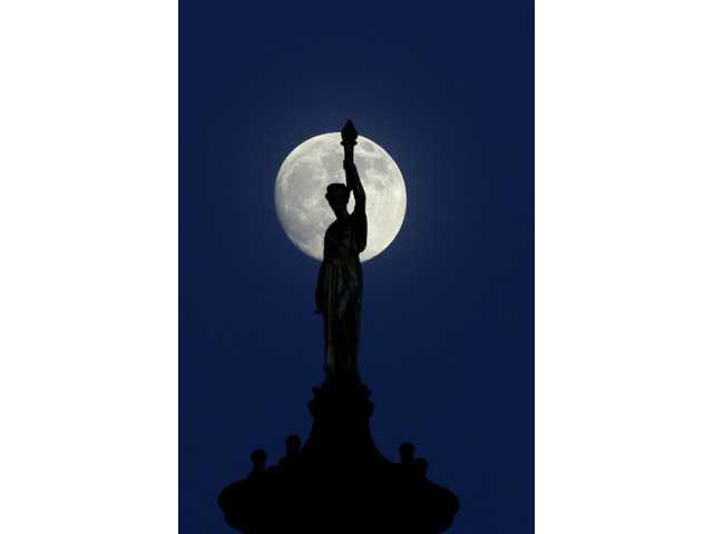 "The moon in its waxing gibbous stage shines behind a statue entitled ""Enlightenment Giving Power"" by John Gelert."