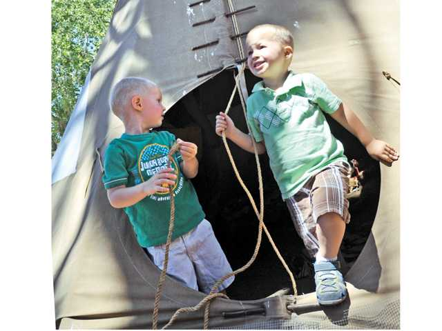 Lake Hughes residents Joey Miedal, 3, and brother Micah, 4, exit a Native American teepee on display at the Powerhouse Firefighters Appreciation Day event held at Shadowland Foundation in Lake Hughes on Saturday.