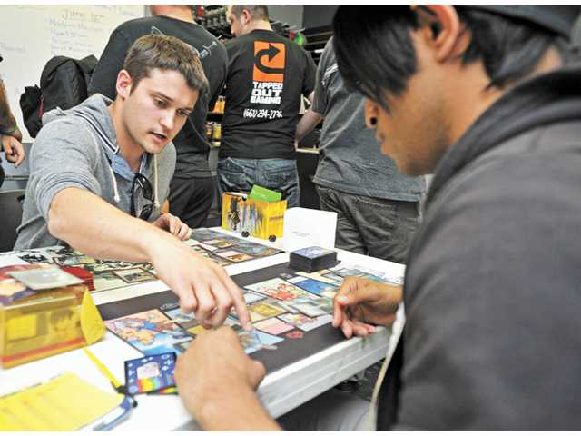 Kyle McCarriher, left, and Oscar Casasola compete in the trading card game Magic: The Gathering at Tapped Out Gaming in Valencia on Saturday.