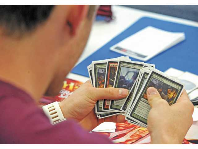 Hunter Jones scans through his cards as he competes in the card game Magic: The Gathering at Tapped Out Gaming in Valencia on Saturday.
