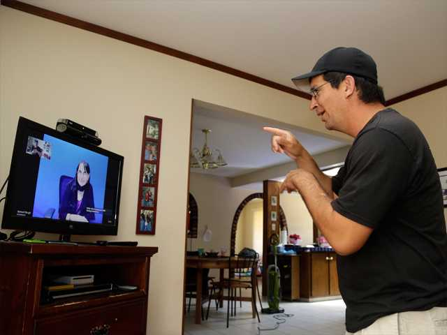 Kevin Bella talks with Mission San Jose head football coach Sam Baugh using the help of a sign language interpreter on a television screen at home in Fremont, Calif., on Thursday.