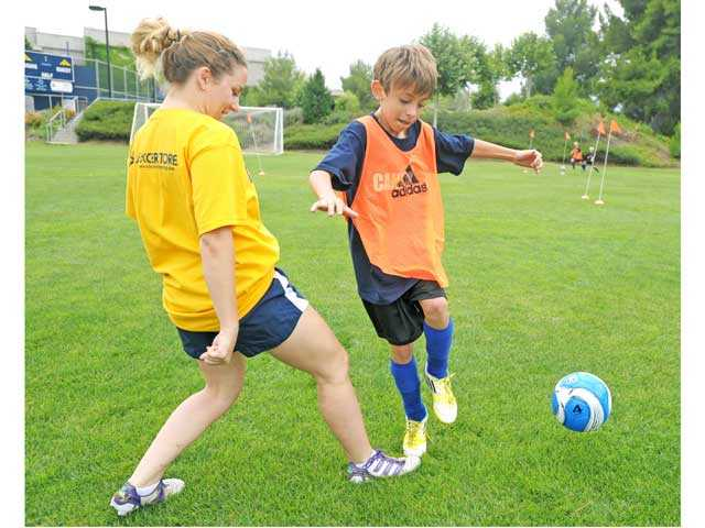 Lauren Amara, left, runs defense on Grant Sterba, 12, as he practices his attack technique in the Cougar Soccer Summer Camp at College of the Canyons in Valencia on Monday. Amara, an incoming freshman at COC, was among the coaches providing drills and activities for participants. Signal photo by Jonathan Pobre