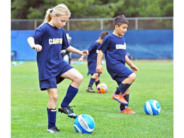 Dakota Baker, 9, left, and Johann Sanchez, 8, practice ball control in the Cougar Soccer Summer Camp at College of the Canyons on Monday. Signal photo by Jonathan Pobre