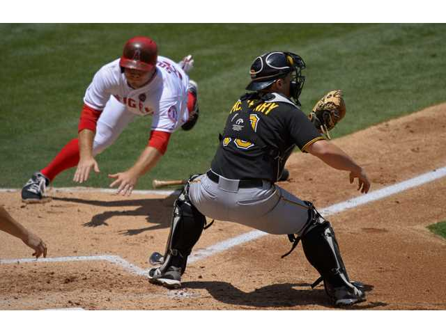 Los Angeles Angels' J.B. Shuck, left scores on a fielders choice by Mike Trout as Pittsburgh Pirates catcher Michael McKenry takes a late throw Sunday in Anaheim.