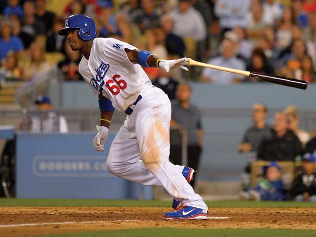 Los Angeles Dodgers' Yasiel Puig hits an RBI single during the eighth inning of their baseball game against the San Francisco Giants, Monday, June 24, 2013, in Los Angeles.