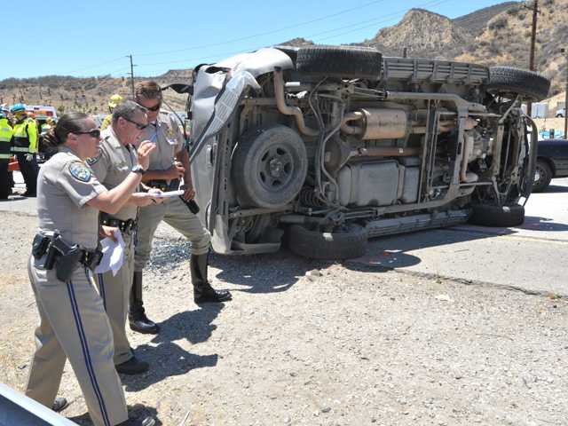 A GMC Yukon SUV is shown on its side as California Highway Patrol officials collect evidence following a two-car crash on Interstate 5 near Parker Road in Castaic. Signal photo by Dan Watson.