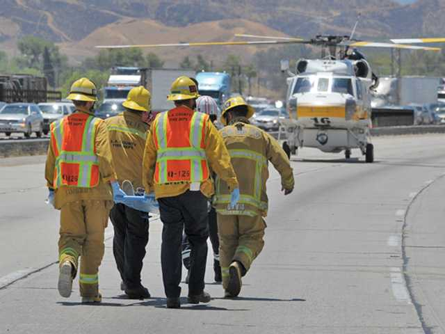 A young boy is carried by paramedics from the Los Angeles County Fire Department to a waiting chopper on the southbound lanes of Interstate 5 near Parker Road in Castaic. The boy was injured in a two-car crash that temporarily blocked traffic in the area. Signal photo by Dan Watson.