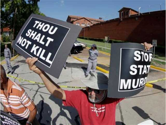 Hadi Jawad holds up his signs to protest the execution of Kimberly McCarthy today outside the Texas Department of Criminal Justice Huntsville Unit, where the death chamber is located, in Huntsville, Texas. If McCarthy is put to death as planned, she would become the 500th person executed in Texas since the state resumed carrying out the death penalty in 1982.