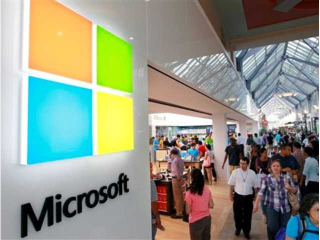 In this Aug. 23, 2012 file photo, the Microsoft Corp. logo, left, is seen on an exterior wall of a new Microsoft store inside the Prudential Center mall, in Boston. The Build conference, which starts today in San Francisco, will give Microsoft's partners a chance to try out the new Windows 8.1 system before it becomes available to the general public.