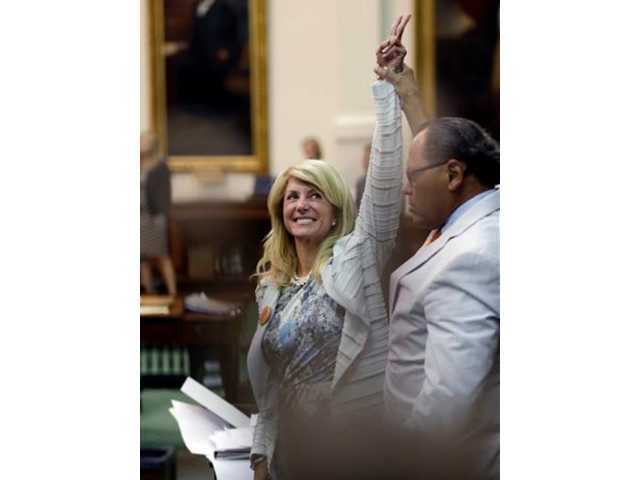 Sen. Wendy Davis, D-Fort Worth, left, who tries to filibuster an abortion bill, reacts as time expires Wednesday in Austin, Texas. Amid the deafening roar of abortion rights supporters, Texas Republicans huddled around the Senate podium to pass new abortion restrictions, but whether the vote was cast before or after midnight is in dispute.