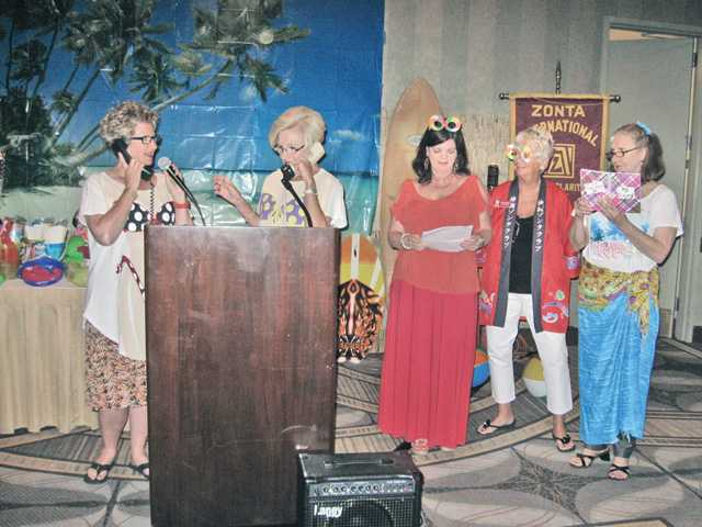 "Zonta International Director Laura Peters, left, takes part in a scripted ""telephone"" chat with, left to right, Jo Ann Rodriguez, Zonta Club of SCV past president, as Cindy Kittle, Past International President Dianne Curtis, and Marilyn Hackett get ready for a ""customized"" Beach Boys musical tribute."