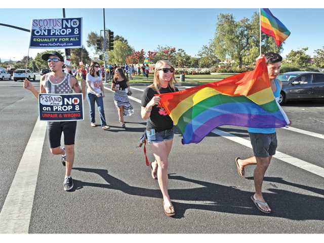 From left, John Anderson, Kelsey Menges and Juan Castanada carry placards and a rainbow flag while joining a group of some 60 same-sex marriage supporters who gathered at the corner of Valencia Boulevard and McBean Parkway in Valencia to celebrate the Supreme Court's ruling on Wednesday. Photo by Dan Watson.