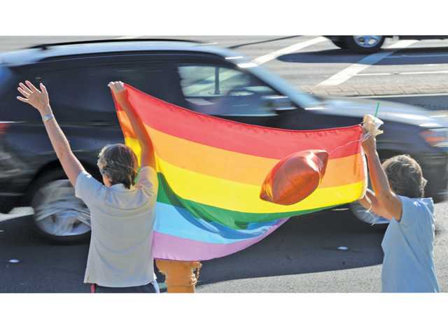 Bestsy Skidmore, left, Seleste Sakato hold up a rainbow flag for passing motorists during the rally on Wednesday. Photo by Dan Watson.