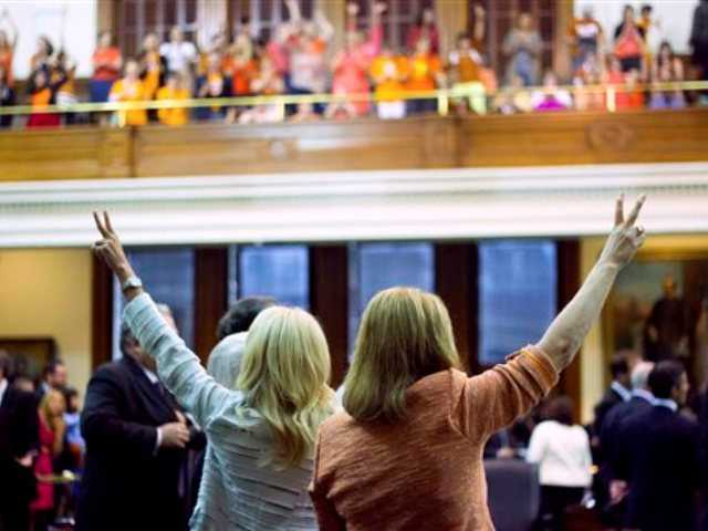 In this Tuesday photo, Texas state Senators Wendy Davis, left, and Sylvia R. Garcia cast their votes against Senate Bill 5 amidst the cheers of the Senate Gallery, in Austin, Texas.