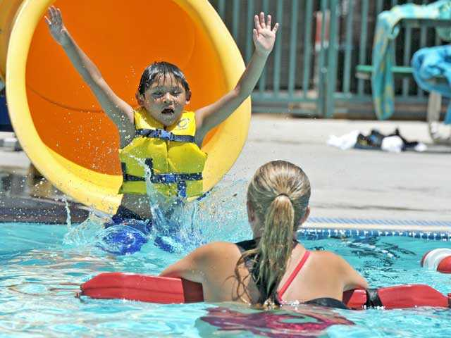 Uriel Flores, 6, slides into the pool at Newhall Park on Thursday. Signal photo by Jonathan Pobre