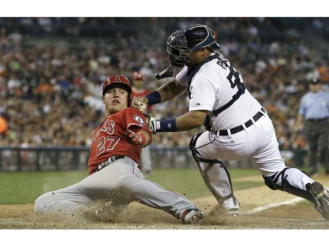 Los Angeles Angel Mike Trout slides safely under the tag of Detroit Tigers catcher Brayan Pena to score on a Josh Hamilton ground out in the seventh inning in Detroit on Wednesday.