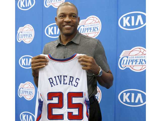Former Boston Celtics head coach Doc Rivers holds his new Los Angeles Clippers jersey during a press conference in Los Angeles on Wednesday.