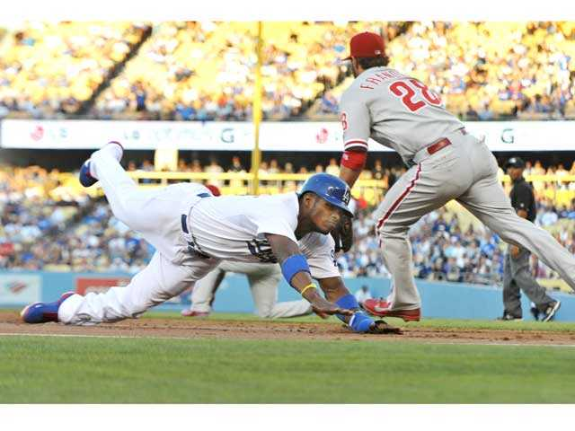 Los Angeles Dodgers' Yasiel Puig slides past Philadelphia Phillies third baseman Kevin Frandsen at third base on Thursday in Los Angeles. Signal photo by Jonathan Pobre
