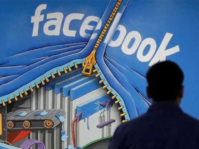 In this Friday, March 15, 2013 file photo, a Facebook employee walks past a sign at Facebook headquarters in Menlo Park.