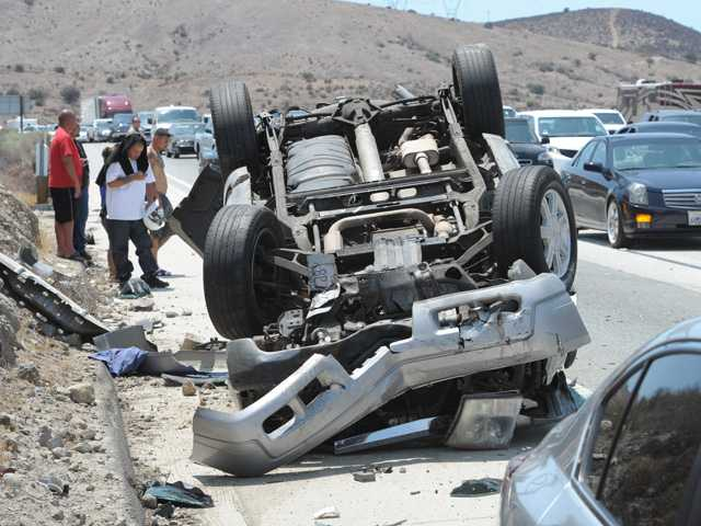 Motorists involved in a crash on the northbound Highway 14 Freeway, south of Agua Dulce Canyon Road stand next to an overturned SUV as traffic is directed around the collision on Saturday afternoon in Agua Dluce. Signal photo by Dan Watson.