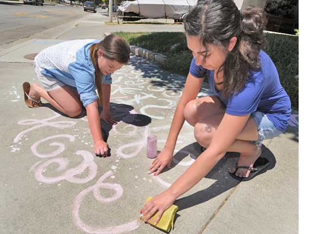 Seventeen-year-olds Sofia Castro, left, and Kylah Diaz got out of their hot house and created artwork on the hot sidewalk. They mixed up their own paint using water, cornstarch and food dye and used sponges to paint a design on the side walk in front of their home Castaic on Friday. Signal photo by Dan Watson.