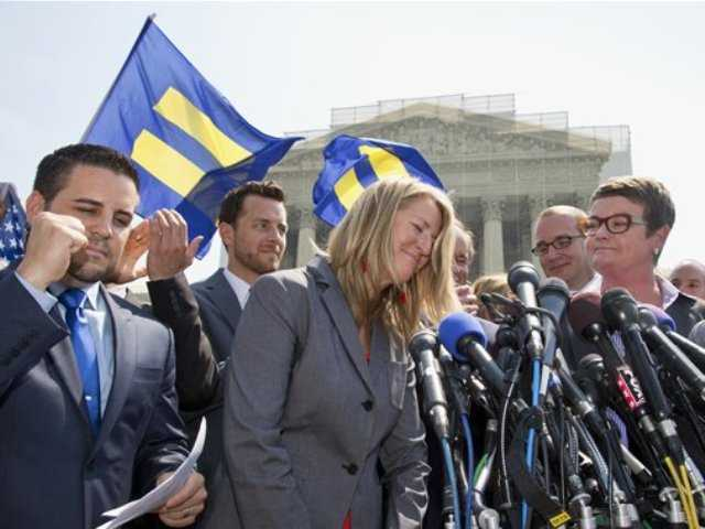 Sandy Stier, center, and her partner Kris Perry, right, plaintiffs in Hollingsworth v. Perry, the California Proposition 8 case, meet with reporters outside the Supreme Court in Washington after the court's 5-4 decision that cleared the way for the resumption of same-sex marriage in their home state of California on Wednesday.