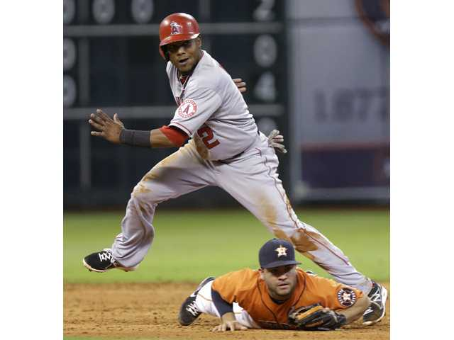 Los Angeles Angel Erick Aybar (2) steps over Houston Astros second baseman Jose Altuve as they watch the ball get away on a throwing error by Astros shortstop Ronny Cedeno on Friday in Houston.