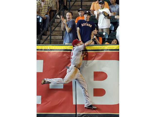 Los Angeles Angels right fielder Josh Hamilton leaps at the wall to make the catch of a fly ball hit by Houston Astro Matt Dominguez Saturday in Houston.