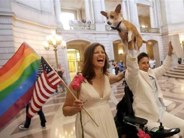 Jen Rainin, left, laughs as her wife Frances holds up their dog Punum after they were married at City Hall in San Francisco, Friday, June 28, 2013.