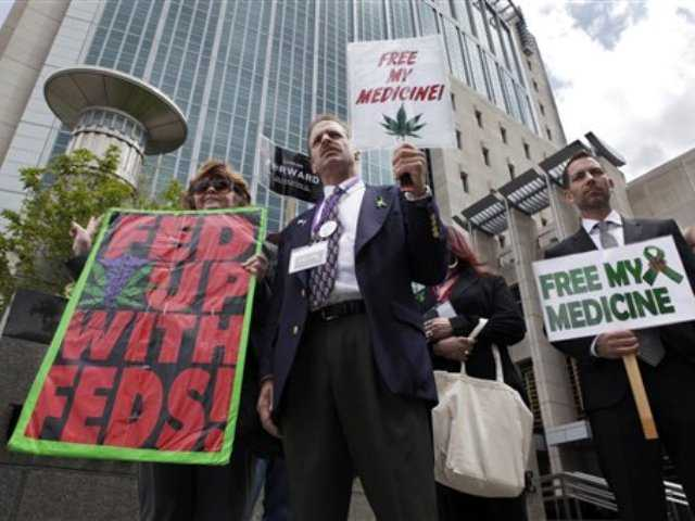 This May 6, 2013 file photo shows medical marijuana demonstrators holding up signs outside of the Federal Courthouse in Sacramento, Calif.