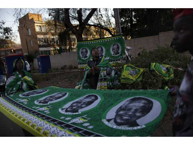 Vendors selling shawls bearing the image of former South African President Nelson Mandela, stands at the entrance to the Mediclinic Heart Hospital where former South African President Nelson Mandela is being treated in Pretoria, South Africa on Friday.