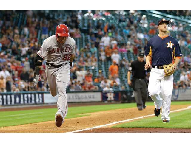 Los Angeles Angels' Josh Hamilton (32) runs toward home to score as Houston Astros third baseman Matt Dominguez, right, watches Sunday in Houston.