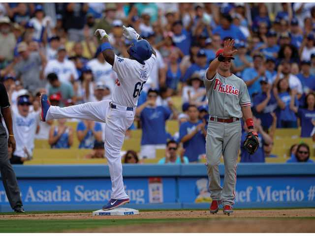 Los Angeles Dodgers' Yasiel Puig, left, points to the sky after hitting a triple as Philadelphia Phillies third baseman Michael Young looks on during the fifth inning Sunday in Los Angeles.