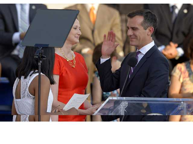 Eric Garcetti, right, is sworn as mayor of Los Angeles by 8th grader Kenia Castillo, left, as his wife Amy Wakeland looks on in front of city hall, Sunday in Los Angeles.