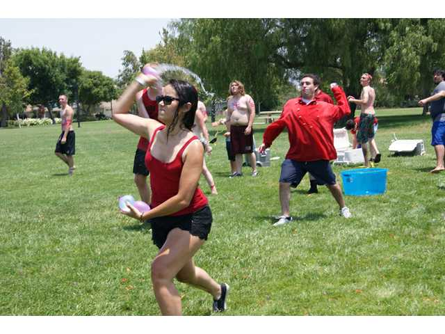 "Members of the ""red coats"" hurl water balloons during the Water Balloon Revolution at Valencia Valley Park on Sunday. The event included about 100 college-age combatants throwing water balloons at each other."