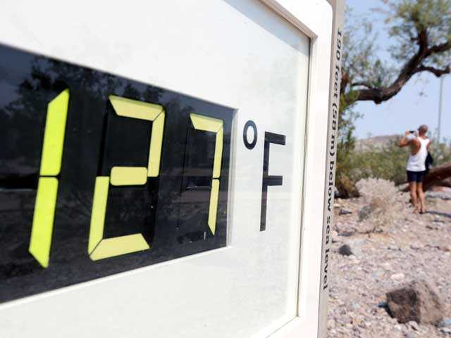 A visitor to the Furnace Creek Vistitor Center walks by a digital thermometer in Death Vally National Park Friday, June 28, 2013 in Furnace Creek, Calif. AP Photo
