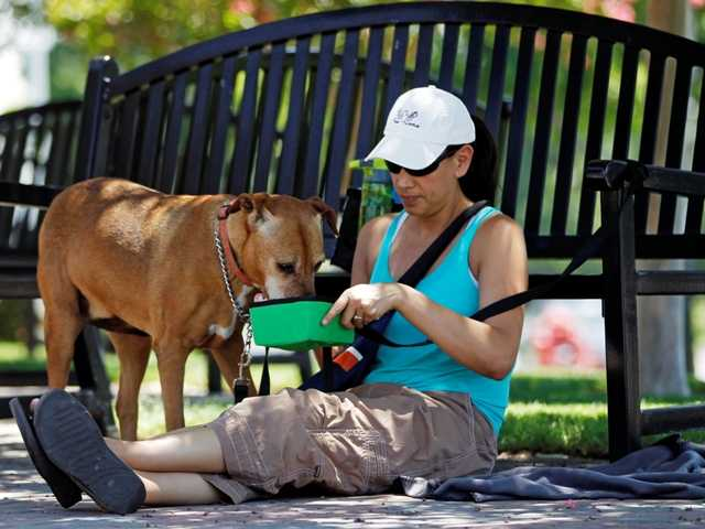 "Monee Hauducoeur, from Upland, Calif., keeps a bowl of fresh water for her dog, ""Summer,"" as she awaits in the shade to adopt another dog on June 28."