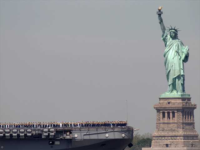 In this May, 2011 file photo, sailors stand on deck of the USS Iwo Jima as it passes Liberty Island and the Statue of Liberty during Fleet Week in New York. After hundreds of National Park Service workers from as far away as California and Alaska spent weeks cleaning and making repairs on the national landmark in the wake of Superstorm Sandy, Liberty Island is scheduled to reopen to the public on Independence Day.