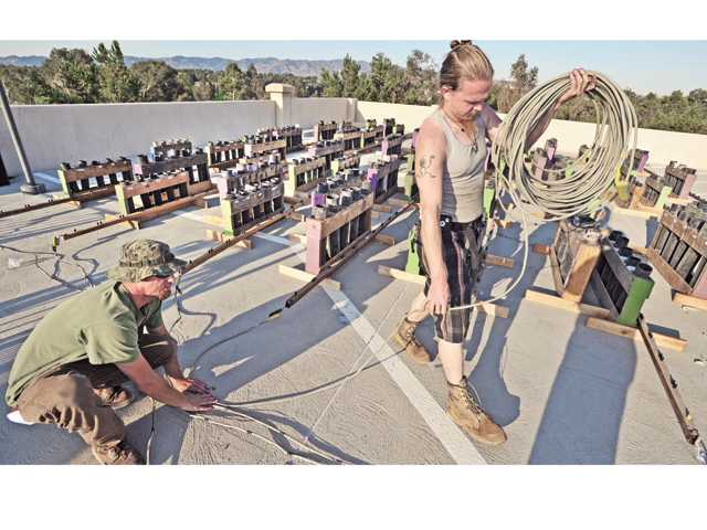 Pyro Spectacular crew members Jon Pirate, left, and Jordan Ryan walk in front of hundreds of mortars as they unroll the firing cables that will be connected to the firing control board on the roof of the Westfield Valencia Town Center parking garage while preparing for Thursday's fireworks show. Signal photo by Dan Watson