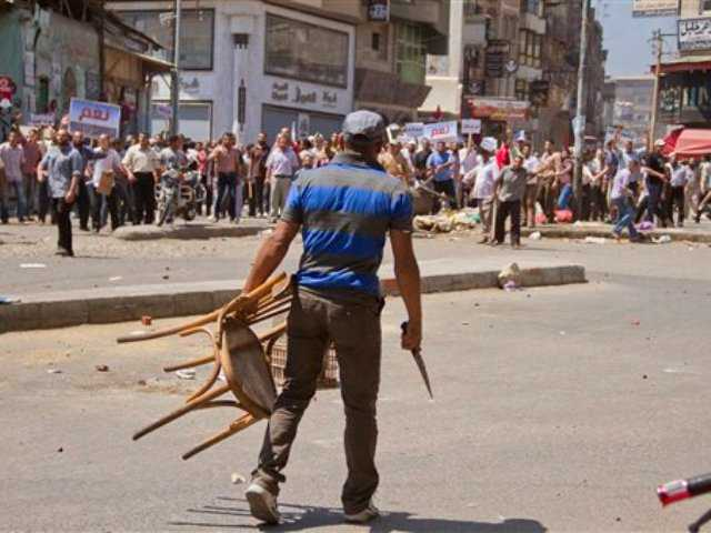 An Egyptian opposition protester holds a chairr and knife during a clash between supporters and opponents of President Mohammed Morsi in downtown Damietta, Egypt, today. The deadline on the military's ultimatum to President Mohammed Morsi has expired, with 48 hours passing since the time it was issued.