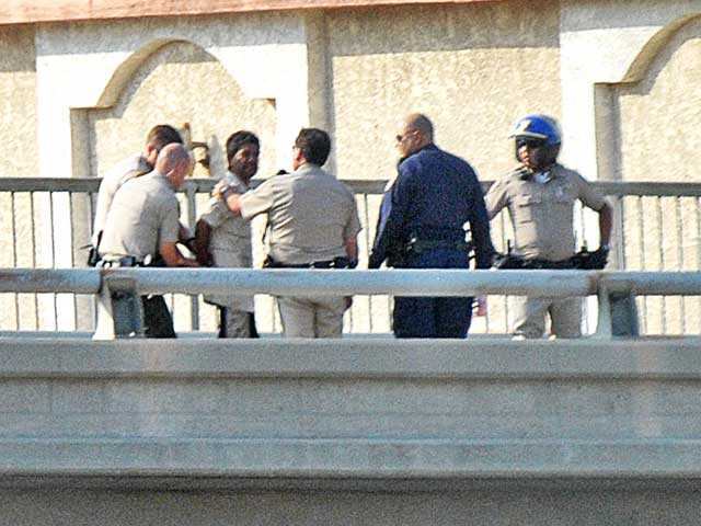 Law enforcement officers detain a man on the Parker Road overpass over Interstate 5 in Castaic after he threatened to jump from the bridge Wednesday. Signal photo by Jonathan Pobre