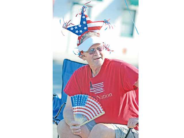Mike Barr of Valencia waits along Main Street in Newhall for the next entry of the 2013 Santa Clarita Fourth of July Parade to pass by. Signal photo by Dan Watson.