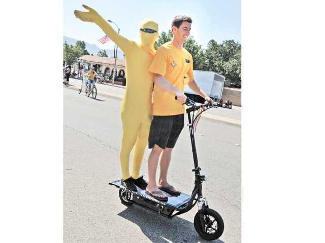 Chris Synnott, left, dressed as the sun and Jeff Figearo ride along on a solar powered scooter next to the SunPower by Green Convergence truck during the 2013 Santa Clarita Fourth of July Parade in Newhall on Thursday. Signal photo by Dan Watson.