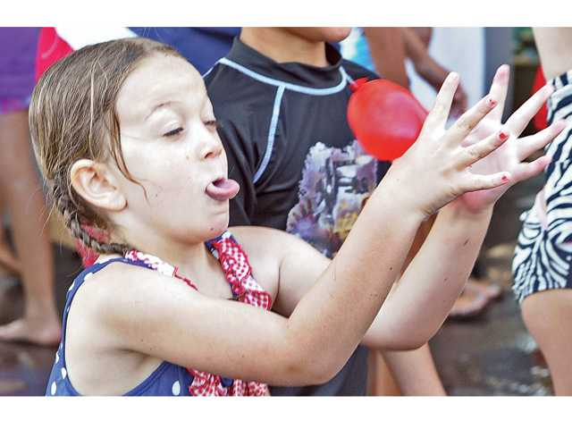 Clara McKeever, 6, of Auga Dulce reaches to catch a water balloon during a water balloon toss game at the SoakFest event on Thursday.Photo by Dan Watson.