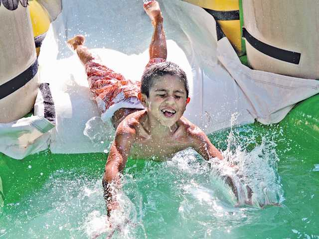 Anthony Gonzalez , 5, zooms down a water slide and head-first into a pool at the SoakFest event held at The Church On The Way Santa Clarita in Valencia on Thursday. Photo by Dan Watson.