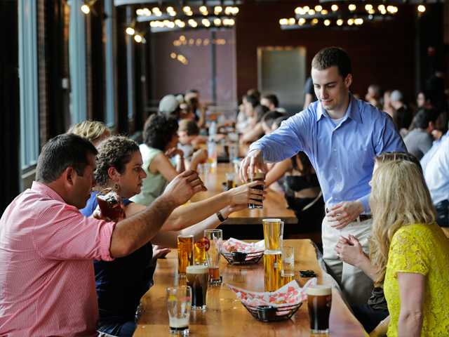 In this July 1 photo, patrons sample a variety of beers at the Beer Hall at the Harpoon Brewery in the Seaport District of Boston. The neighborhood around the brewery is transforming from a waterfront industrial area to one that hosts upscale restaurants, luxury hotels and an art museum.