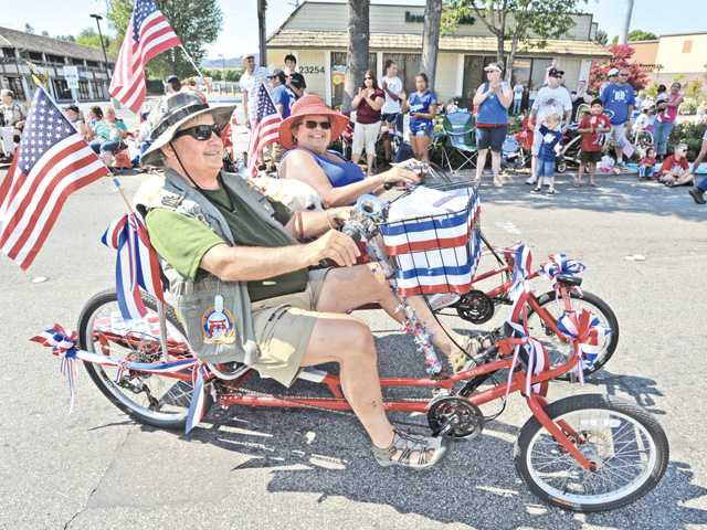 "Jim and Pam Hogan pedal along behind the Vietnam Veterans ""The Lost Patrol "" Color Guard during the 2013 Santa Clarita Fourth of July Parade in Newhall on Thursday. The entry won first place in Color Guard. Signal photo by Dan Watson"