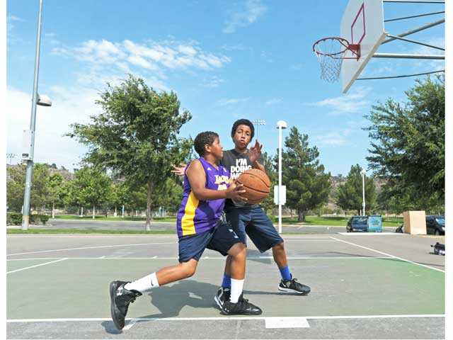 Adrian McIntyre, 11, left, and brother Anthony, 13, practice at the basketball courts at Central Park in Saugus on Friday. Signal photo by Jonathan Pobre